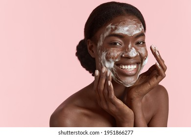 Beautiful black girl wash her face with cleansing face foam. Happy young woman looking at camera. Concept of face skin care. Isolated on pink background. Studio shoot