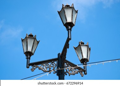 Beautiful black glass street lamp with three lanterns. Photographed close-up on the background of blue sky