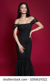 Beautiful black hair woman in black dress posing against red background