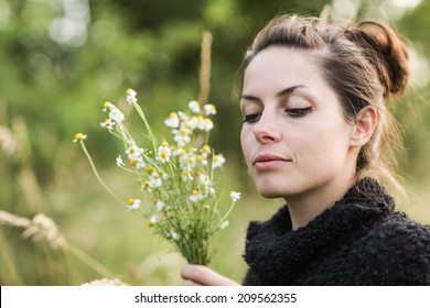 Beautiful black hair woman enjoying field, pretty girl relaxing outdoor, holding plant, happy young lady and spring green nature. Low depth of field.