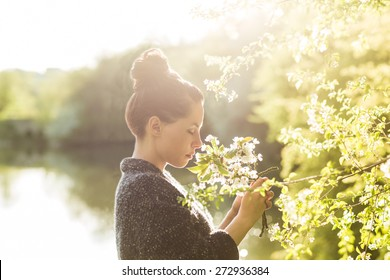Beautiful black hair woman enjoying blooming tree from profile, pretty girl relaxing outdoor.  Happy young lady and spring green nature. Low depth of field. Strong back light.