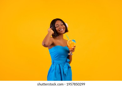 Beautiful black lady in casual outfit holding tropical summer cocktail and listening to music in headphones on orange background. Lovely African American woman with refreshing drink enjoying song