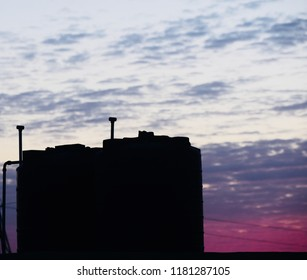 Beautiful black large water tanks with reddish cloudy sky unique photo