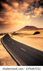 Beautiful black long road for travel conpcept with sand desert dunes on the sides and mountin in the beakcgorund - sunset warm cloudy sky - scenic landscape for travleing with car vacation adventure