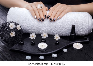 beautiful black manicure with apricot flower,candles and towel on the wooden table. spa