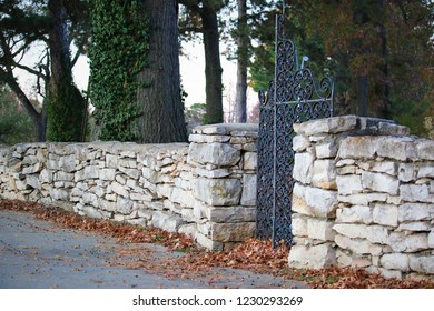 A beautiful black metallic gate with intricate design, established in stone wall boundaries. The background has huge trees and some fallen leaves are accumulated along the base of wall o the side walk