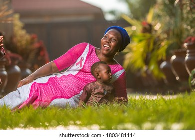 Beautiful black mother with child wearing African costume with pink ribbon craft on her chest for breast cancer campaign-concept on maternal breast cancer awareness