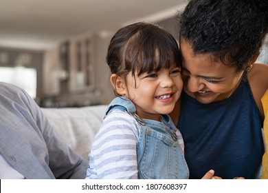 Beautiful black mother embracing little girl sitting on couch with copy space. Cute daughter hugging african mother and smiling together. Happy mom jokes with her kid at home and playing together.