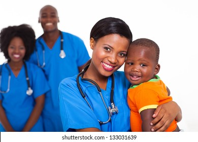 beautiful black pediatrician and baby boy with co-workers on background