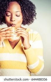 Beautiful black person eating hamburger sandwich