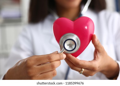 Beautiful black smiling female doctor hold in arms red toy heart closeup. Cardio therapeutist student education CPR 911 life save physician make cardiac physical pulse rate measure arrhythmia