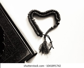 Beautiful black and white the holy Quran and tasbeeh bead heart shape with white background.
