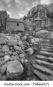 Beautiful black and white  landscape image of St Govan's Chapel on Pemnrokeshire Coast in Wales