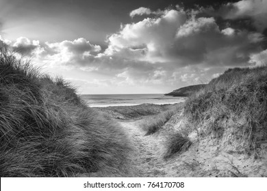 Beautiful black and white landscape image of Freshwater West beach with sand dunes in Pembrokeshire Wales
