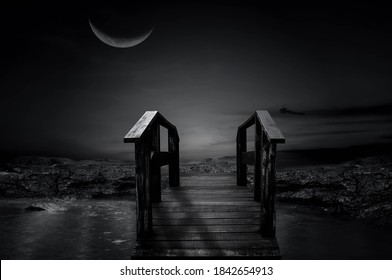 Beautiful black and white photo of the wooden bridge in the night of the half moon