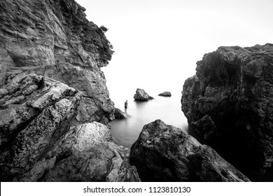 Beautiful black and white rocky beach landscape. Silhouette of man in swimwear on the stone, ready to dive into the sea.
