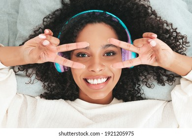 Beautiful black woman with afro curls hairstyle.Smiling model in sweater and jeans.Sexy carefree female listening music in wireless headphones in the morning.Lying in bed in white interior. Top view - Shutterstock ID 1921205975