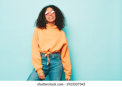 Beautiful black woman with afro curls hairstyle.Smiling model in orange hoodie and trendy jeans clothes. Sexy carefree female posing near blue wall in studio. Tanned and cheerful in sunglasses