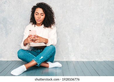 Beautiful black woman with afro curls hairstyle.Smiling model in white trendy jeans clothes. Sexy carefree female sitting on the floor near gray wall in studio.Looking at cellphone. Using apps
