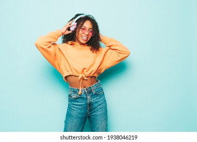 Beautiful black woman with afro curls hairstyle.Smiling model in orange hoodie and jeans.Sexy carefree female listening music in wireless headphones.Posing in studio near blue wall - Shutterstock ID 1938046219