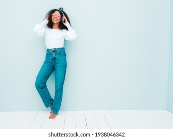 Beautiful black woman with afro curls hairstyle.Smiling model in sweater and jeans.Sexy carefree female listening music in wireless headphones.Posing in studio near light blue wall in sunglasses