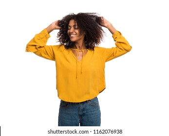 Beautiful black woman with afro hair in yellow autumn top having fun smiling and dancing in studio against white background.