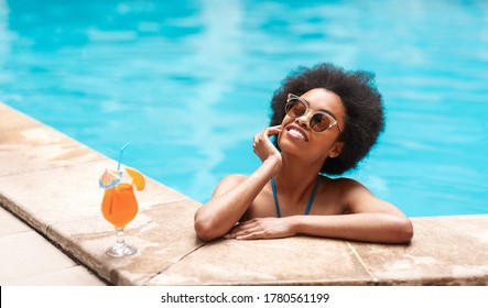 Beautiful black woman in blue bikini and sunlasses relaxing in swimming pool with cocktail drink, copy space. Panorama