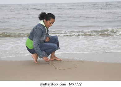 Beautiful black woman drawing a heart on the beach