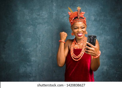 beautiful black woman dressed in traditional edo tribe of nigeria bridal attire feeling excited and jubilant while viewing something on her phone