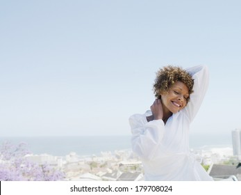 Beautiful black woman dressing white at morning against clear blue sky