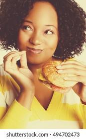Beautiful black woman eating burger sandwich