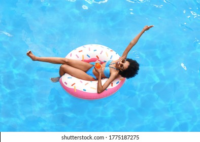 Beautiful black woman with glass of summer cocktail on inflatable ring at pool, above view