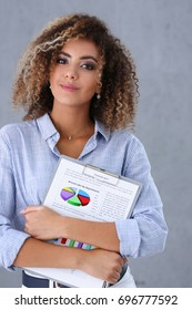 Beautiful black woman portrait. Holds a clipboard with financial statistics fashion style mulatto curly hair with white locks eye view of the camera