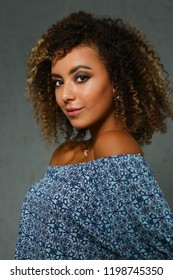 Beautiful black woman portrait. Worth a gray background and smiling beauty fashion style curly hair with white strands view of the eye in the camera