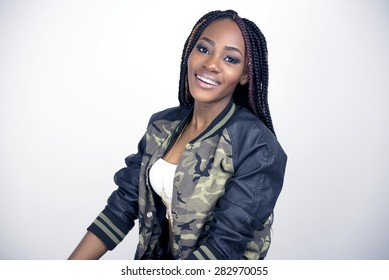 Beautiful black woman posing in a studio wearing a white tube top, camo jacket, heels and jeans.