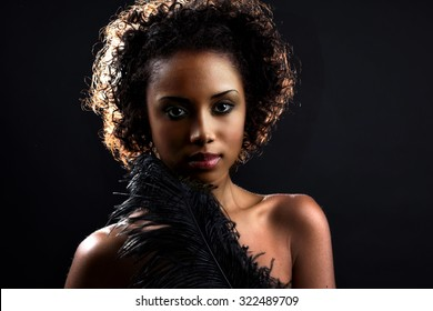 Beautiful black woman posing in a studio. Perfect makeup. Beauty fashion. Close-up portrait of attractive young model with bright make-up.