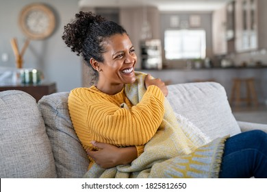 Beautiful black woman sitting on couch wrapped under blanket and laughing. Cheerful african american woman relaxing at home. Carefree and happy mid lady hugging herself with warm blanket in winter.