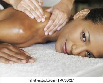 Beautiful black woman at spa being massaged