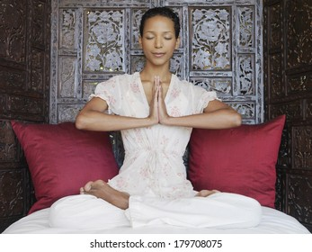 Beautiful black woman at spa meditating and practicing yoga