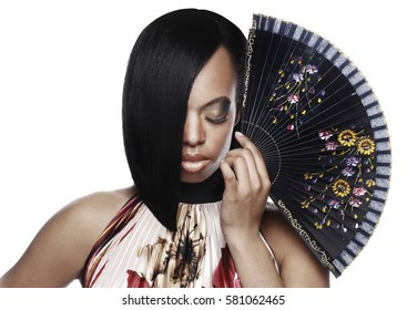 Beautiful black woman with a stylish hair cut looking down and holding a fan