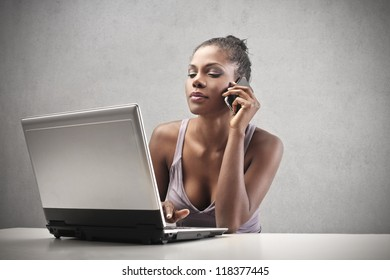 Beautiful black woman using a smart-phone and a laptop computer