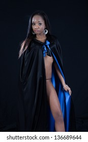Beautiful black woman wearing a cape that is black on the outside and blue on the inside, with no blouse on underneath the cape, displaying a bit of her abdomen and her shapely leg