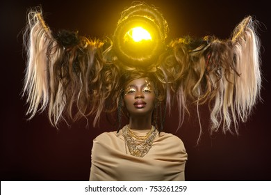 beautiful black young woman with art hair composition and gold makeup. golden goddess.  beauty studio shot on dark background. copy space.