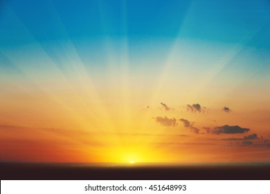 Schöne strahlende Sonnenuntergangslandschaft über der Wiese und orangefarbener Himmel darüber. Erstaunlicher Sommersonnenaufgang als Hintergrund.