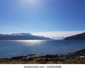 beautiful ble ocean view with snow covered mountain range and greenery on the dyroy island in the northern Norway wilderness