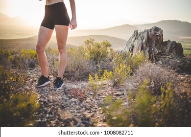 Beautiful blind fitness model stretching outside in nature before a trail run in the hills