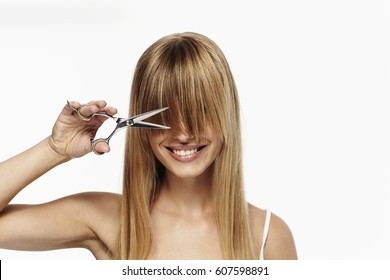 Beautiful blond about to cut hair, studio