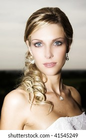 Beautiful Blond bride with blue eyes wearing diamond jewelery