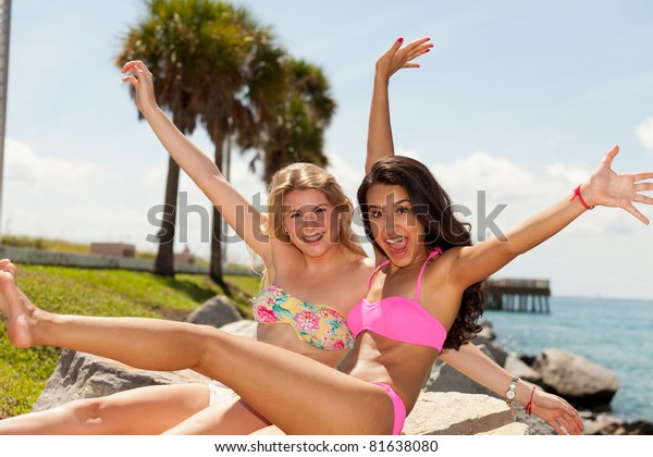 Beautiful blond and brunette young women enjoying South Pointe Park in Miami Beach.