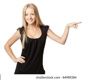 Beautiful blond business woman in black dress pointing at copy space over white background